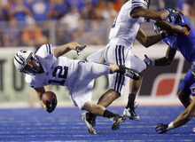 Brigham Young's JD Falslev (12) is tripped up during the first half of an NCAA college football game against Boise State on Thursday, Sept. 20, 2012, in Boise, Idaho. (AP Photo/The Idaho Statesman, Joe Jaszewski)