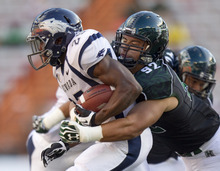 Nevada running back Stefphon Jefferson (25) is tackled from behind by Hawaii defensive lineman Beau Yap (92) in the first quarter of an NCAA college football game Saturday, Sept. 22, 2012, in Honolulu. (AP Photo/Eugene Tanner)