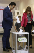Georgian President Mikhail Saakashvili, left, and his wife Sandra Roelofs, right, cast their ballots as their son Nikoloz stands beside them at a polling station in Tbilisi, Georgia, Monday, Oct. 1, 2012. Voters in Georgia are choosing a new parliament in a heated election Monday that will decide the future of Saakashvili's government. (AP Photo/Efrem Lukatsky)