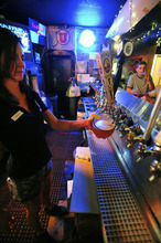 Stephen Speckman | For The Salt Lake Tribune O'Shucks Bar & Grill bartender Hadley Hege serves up a schooner of Moab Over The Top Hefeweizen beer as pub crawler Sean Lang tips a cold one during the Utah Heritage Foundation's Thirst Fursdays Historic Pub Crawl, held Sept. 6 and on the first Thursday of each month.