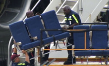 In this photo provided by WBZ-TV seats from an American Airlines 757 are carried before receiving