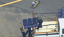 In this photo provided by WBZ-TV and WFXT-TV seats from an American Airlines 757 are carried before receiving