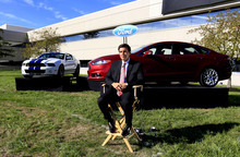 FILE-In this Sept. 10, 2012, file photo, Mark Fields, Ford president of the Americas, poses for a photo next to a 2013 Fusion at the Flat Rock Assembly in Flat Rock, Mich. Interest rates are low, trade-in values are high, and automakers are rolling out attractive new cars and trucks in key areas. All of these factors combined to keep auto sales strong in September. Automakers report U.S. sales figures throughout the day on Tuesday, Oct. 2, 2012. (AP Photo/Carlos Osorio, File)
