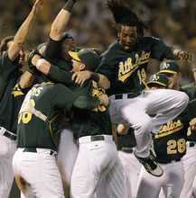 Oakland Athletics, including Jemile Weeks (19), celebrate after clinching a wild card berth in the American League at the end of a baseball game against the Texas Rangers on Monday, Oct. 1, 2012, in Oakland, Calif. (AP Photo/Ben Margot)