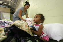 Steve Griffin | The Salt Lake Tribune   Rachel Jeffers and her one-year-old daughter, Keiana, prepare their sleeping area at the Midvale shelter in Midvale, Utah Monday October 1, 2012.  The winter overflow shelter is opening early this year due to the influx of homeless families the downtown Road Home shelter received this summer.