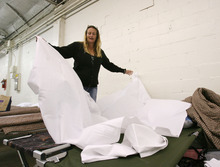 Steve Griffin | The Salt Lake Tribune   Michelle Webster unfolds sheets as she makes up her cots she and her five-year-old son will be sleeping on at the Midvale shelter in Midvale, Utah Monday October 1, 2012.  The winter overflow shelter is opening early this year due to the influx of homeless families the downtown Road Home shelter received this summer.