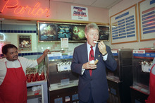 Democratic presidential candidate Bill Clinton samples some ice cream at a parlor called The Cookie Jar during a campaign stop in West Philadelphia, Oct. 12, 1992. At left is the shop owner Curtis Lamar. (AP Photo/J. Scott Applewhite)