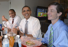 President Barack Obama, flanked by Assistant to the President and Director of Legislative Affairs Rob Nabors, left, and Chief of Staff to the Vice President Bruce Reed,  eats lunch at the Good Stuff Eatery in Washington, Wednesday, Aug. 3, 2011. (AP Photo/Susan Walsh)