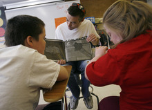 Francisco Kjolseth  |  The Salt Lake Tribune Chad Winter, center, reads a book for 12-year-olds Nathan Perkins, left, and Angel Funk in Ms. Lisa Seipert's special needs class at Kearns Junior High on Thursday, September 13, 2012. Volunteers from 3M Health Information Systems and Holland & Hart helped clean up the grounds and helped tutor students in math and reading as part of the state-wide United Day of Caring.