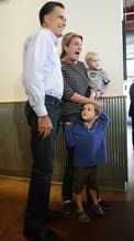 Republican presidential candidate and former Massachusetts Gov. Mitt Romney poses for a photo with customers as he makes an unscheduled stop at a Chipotle restaurant in Denver, Tuesday, Oct. 2, 2012. (AP Photo/Charles Dharapak)