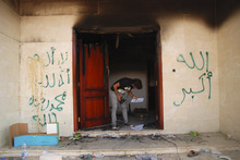 A man looks at documents at the U.S. consulate in Benghazi, Libya, after an attack that killed four Americans, including Ambassador Chris Stevens, Wednesday, Sept. 12, 2012. The graffiti reads,