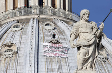 Firefighters look at Italian businessman Marcello di Finizio standing above his banner  which reads in Italian