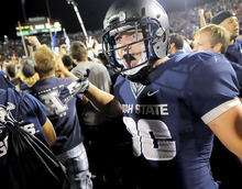 Utah State safety McKade Brady celebrates with fans after the Aggies defeated Utah 27-20 in overtime, Friday, Sept. 7, 2012, in Logan, Utah. (AP Photo/The Herald Journal, Eli Lucero)