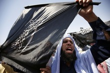 FILE - In this Saturday, April 21, 2012 file photo, a follower of Egyptian Muslim cleric and former candidate for the presidency Hazem Abu Ismail holds an Islamist flag that reads,