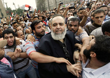 FILE - In this Friday, Oct. 28, 2011 file photo, Egyptian Muslim cleric and candidate for the Egyptian presidency Hazem Salah Abu Ismail, center, is guarded by his supporters as he enters Tahrir Square during a protest against the ruling military council, in Cairo, Egypt. Internal divisions are threatening to unravel Egypt's second biggest political party, the political arm of the ultraconservative Salafis, the country's most hardline Islamist movement. The party came out of nowhere after Mubarak's fall to win the second largest number of seats in parliament, demonstrating the hidden strength of Salafis on the street. But now its leaders are split over whether Muslim clerics or more pragmatic politicians should be steering the movement. (AP Photo/Amr Nabil, File)