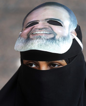 FILE - In this Wednesday, April 11, 2012 file photo, an Egyptian woman wears a mask of a potential candidate presidential candidate Hazem Abu Ismail as she attends a support rally outside a courtroom in Cairo, Egypt. Internal divisions are threatening to unravel Egypt's second biggest political party, the political arm of the ultraconservative Salafis, the country's most hardline Islamist movement. Now its leaders are split over whether Muslim clerics or more pragmatic politicians should be steering the movement.  (AP Photo/Khalil Hamra, File)