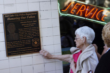 Francisco Kjolseth  |  The Salt Lake Tribune Maurine Clark touches the plaque honoring her husband's service as a detective before he was shot and killed during an armed robbery 39 years ago. The Salt Lake Police Department gathered at 564 E. Third Ave. in Salt Lake City on Thursday, October 4, 2012, to dedicate the plaque at the Avenues Bistro on Third, which used to be a pharmacy back in 1973 where an armed robbery led to his death.