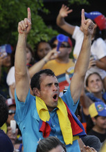 Opposition presidential candidate Henrique Capriles  gestures from the top of a vehicle during a campaign rally in Maracaibo, Venezuela, Wednesday, Oct. 3, 2012. Capriles will run against President Hugo Chavez in the presidential elections Oct. 7. (AP Photo/Ariana Cubillos)