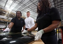 FILE-In this Monday, Aug. 13, 2012, file photo, quality specialist Teri Evans, left, and packer Wendy Jackson, right, check a window pane as quality manager Sebastian Kahle looks on during a tour of the SKD packaging facility at BLG Logistics, Inc. in Vance, Ala. Orders to U.S. factories fell in August, mostly because of a sharp drop in volatile aircraft orders. The decline offset an increase in orders that reflect corporate investment plans.  (AP Photo/Tuscaloosa News, Dusty Compton, File)