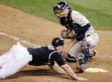 FILE - In this Oct. 1, 2007, file photo, San Diego Padres catcher Michael Barrett, right, tries to put a tag on Colorado Rockies' Matt Holliday as Holliday scores the winning run in their baseball game in Denver. Replays were inconclusive on whether Holliday actually touched the plate while scoring the winning run, but he was called safe, and the Rockies won 9-8 in 13 innings. The Associated Press takes a look at the nine one-game playoffs in major league history. (AP Photo/Will Powers, File)