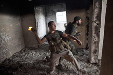 Free Syrian Army soldier throws a petrol bomb against Syrian Army positions  in Saif Al Dawle district in Aleppo, Syria, Wednesday, Oct. 3, 2012. Three suicide bombers detonated cars packed with explosives in a government-controlled area of the battleground Syrian city of Aleppo on Wednesday, killing at least 34 people, leveling buildings and trapping survivors under the rubble, state TV said. More than 120 people were injured, the government said. (AP Photo / Manu Brabo)