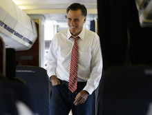 Republican presidential candidate, former Massachusetts Gov. Mitt Romney smiles as he speaks to advisers and staff members on his campaign plane in Denver, Thursday, Oct. 4, 2012. (AP Photo/Charles Dharapak)