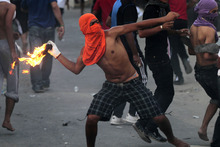 A Bahraini anti-government protester throws a petrol bomb toward riot police, unseen, firing tear gas and stun grenades in Sadad, Bahrain, on Wednesday, Oct. 3, 2012. Clashes erupted at the end of a mourning procession for Ali Hussein Niema, 17, who allegedly was shot dead last week by riot police. (AP Photo/Hasan Jamali)
