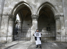 A demonstrator holds a banner against the extradition of Adel Abdul Bari, outside The Royal Courts of Justice in London Friday, Oct. 5, 2012. Britain's High Court is set to rule Friday afternoon on whether radical cleric Abu Hamza al-Masri and four other terrorist suspects can be extradited to the United States — judgments the government hopes will clear the final hurdle to their removal after years of legal wrangling.(AP Photo/Kirsty Wigglesworth)