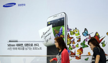 Visitors walk by a billboard of Samsung Electronics's product at a showroom of its headquarters in Seoul, South Korea, Friday, Oct. 5, 2012. Samsung Electronics Co. tipped all-time high quarterly operating profit, likely driven by strong sales of high-end smartphones that offset weak semiconductor orders. (AP Photo/Lee Jin-man)