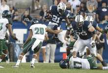 Chris Detrick  |  The Salt Lake Tribune BYU running back Jamaal Williams runs past Hawaii Warriors cornerback Ne'Quan Phillips (20) and linebacker Kamalani Alo (47) on Sept. 28, 2012.