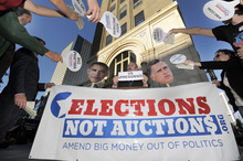 IMAGE DISTRIBUTED FOR AVAAZ ELECTIONS NOT AUCTIONS CAMPAIGN - A crowd posing as Super PACs, corporate sponsors and wealthy donors bid for political races during Avaaz's Elections not Auctions campaign event, Tuesday, Oct. 2, 2012, in Denver. The campaign is urging candidates to amend big money out of politics. (Jack Dempsey/AP Images for Avaaz Elections not Auctions Campaign)