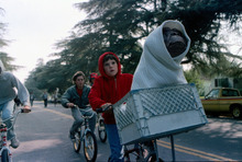 This undated publicity film image released by Universal Pictures shows Henry Thomas as Elliott and E.T. in a basket on a bicycle in a scene from director Steven Spielberg's