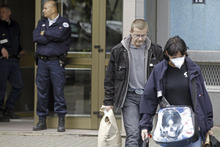 French police officers, left, stand guard at the entrance of a building in Strasbourg, France, Saturday Oct. 6, 2012, as plainclothed policemen carrying clues, right, leave, after a suspect was shot dead for firing at police. French anti-terrorism forces carried out raids in cities nationwide on Saturday, at least five people were arrested in the investigation into the firebombing of a kosher grocery outside Paris last month. (AP Photo/Jean Francois Badias)
