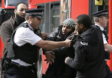 Demonstrators clash with police officers outside The Royal Courts of Justice in London Friday, Oct. 5, 2012. Britain's High Court is set to rule Friday afternoon on whether radical cleric Abu Hamza al-Masri and four other terrorist suspects can be extradited to the United States — judgments the government hopes will clear the final hurdle to their removal after years of legal wrangling. (AP Photo/Kirsty Wigglesworth)