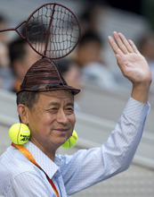 A Chinese man wears an iron-made tennis racquet-shaped hat and tennis ball ear rings while watching a match between Spain's Feliciano Lopez and Jo-Wilfried Tsonga of France in the men's singles semifinal match of the China Open tennis tournament in Beijing Saturday, Oct. 6, 2012. (AP Photo/Andy Wong)