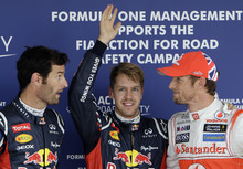 Red Bull driver Sebastian Vettel of Germany, center, celebrates after taking pole position in qualifying for the Japanese Formula One Grand Prix, as second placed Red Bull driver Mark Webber of Australia, left, and third placed McLaren driver Jenson Button of Britain chat, at the Suzuka Circuit in Suzuka, Japan, Saturday, Oct. 6, 2012. (AP Photo/Greg Baker)