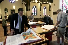 Kim Raff   The Salt Lake Tribune Kyle Anderson looks through Prophets, one of the books in the reproduction of the St. John's Bible on display at the Cathedral Church of St. Mark in Salt Lake City on Oct. 3, 2012. The Bible was produced by St. John's Abbey and University, Collegeville, Minn. Renowned calligrapher Donald Jackson and a team of fellow artists and scribes were commissioned to produce this handwritten, hand-illuminated Bible whose seven volumes measure two feet high and three feet wide when opened.