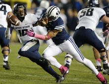Utah State's quarterback Chuckie Keeton, left, is sacked by  BYU's Teu Kautai during the second half of an NCAA college football game at LaVell Edwards Stadium, Friday, Oct. 5, 2012, in Provo, Utah. BYU beat Utah Sate 6-3. (AP Photo/George Frey)