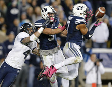 BYU's Preston Hadley, right, intercepts the ball from Utah State's Matt Austin, left, as BYU's Dylan Collie, center, looks on during the second half of an NCAA college football game at LaVell Edwards Stadium, Friday, Oct. 5, 2012, in Provo, Utah. BYU beat Utah Sate 6-3. (AP Photo/George Frey)