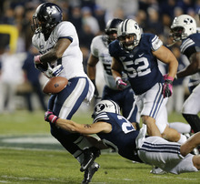 Utah State's Robert Marshall, left, fumbles the ball as he is tackled by BYU's Craig Bills during the second half of an NCAA college football game at LaVell Edwards Stadium, Friday, Oct. 5, 2012, in Provo, Utah. BYU beat Utah Sate 6-3. (AP Photo/George Frey)