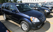 In this Aug. 20, 2006 photo, a long line of unsold 2006 Honda CRVs sits on the lot of a Honda dealership in the south Denver suburb of Littleton, Colo. Honda Motor Co. is recalling CR-V crossovers from the 2002 to 2006 model years because an electrical switch in the driver's side door could melt and cause a fire. Honda and the National Highway Traffic Safety Administration announced the recall Saturday, Oct. 6, 2012. (AP Photo/David Zalubowski)