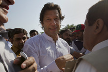 Pakistan's ex-cricket star-turned-politician Imran Khan, center, is surrounded by his supporters as he arrives to lead what organizers are calling the