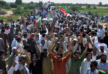 Supporters Pakistan's cricket star turned politician Imran Khan's party, not pictured, raise their hands during a peace march on the outskirts of Tank, Pakistan, Sunday, Oct. 7, 2012. The Pakistani military blocked a convoy carrying thousands of Pakistanis and a small contingent of U.S. anti-war activists from entering a lawless tribal region along the border with Afghanistan on Sunday to protest American drone strikes. (AP Photo/Mohammad Hussain)