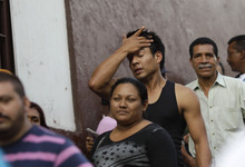 A man wipes his forehead as he waits in line with other voters at a polling station during the presidential election in Caracas, Venezuela, Sunday, Oct. 7, 2012. President Hugo Chavez is running against opposition candidate Henrique Capriles. (AP Photo/Ariana Cubillos)