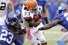 Cleveland Browns running back Trent Richardson (33) is tackled by New York Giants linebacker Spencer Paysinger (52) and Corey Webster (23) during the first half of an NFL football game Sunday, Oct. 7, 2012, in East Rutherford, N.J. (AP Photo/Kathy Willens)