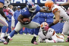 Cleveland Browns linebacker Marcus Benard, right, tackles New York Giants running back Ahmad Bradshaw (44) during the first half of an NFL football game Sunday, Oct. 7, 2012, in East Rutherford, N.J. (AP Photo/Kathy Willens)