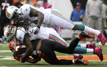 Cincinnati Bengals wide receiver A.J. Green, bottom, is tackled by Miami Dolphins strong safety Chris Clemons and free safety Reshad Jones, top, after a gain in the first half of an NFL football game, Sunday, Oct. 7, 2012, in Cincinnati. (AP Photo/Tom Uhlman)