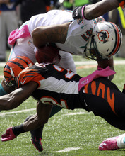 Miami Dolphins fullback Jorvorskie Lane (41) fumbles the ball as he is hit by Cincinnati Bengals cornerback Nate Clements (22) in the first half of an NFL football game on Sunday, Oct. 7, 2012, in Cincinnati. Cincinnati recovered the fumble. (AP Photo/Tom Uhlman)