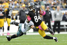 Pittsburgh Steelers wide receiver Antonio Brown (84) tries to evade Philadelphia Eagles cornerback Nnamdi Asomugha (24) after a catch in the second quarter of an NFL football game on Sunday, Oct. 7, 2012, in Pittsburgh. (AP Photo/Don Wright)