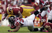 Atlanta Falcons running back Michael Turner (33) is stopped by Washington Redskins inside linebacker London Fletcher, top, and cornerback Richard Crawford (39) during the first half of an NFL football game in Landover, Md., Sunday, Oct. 7, 2012. (AP Photo/Evan Vucci)